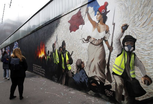 """(AP Photo/Christophe Ena). Women watch a mural by street artist PBOY depicting Yellow Vest (gilets jaunes) protestors inspired by a painting by Eugene Delacroix, """"La Liberte guidant le Peuple"""" (Liberty Leading the People), in Paris, Thursday, Jan. 10, ..."""