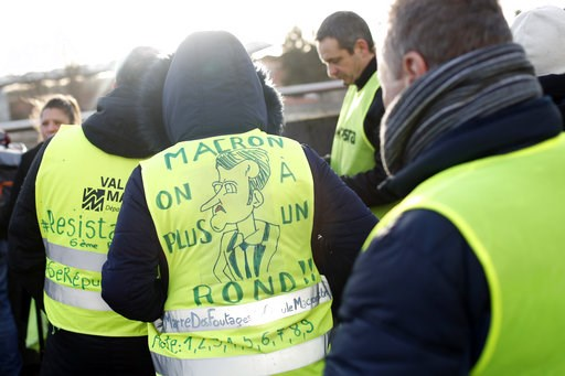"""(AP Photo/Thibault Camus). A protestor wears a yellow jacket reading """"Macron we don't have any more money"""" during a demonstration of unionist and yellow vests, in Creteil, outside Paris, Wednesday, Jan. 9, 2019. About 200 protesters, including unionist..."""