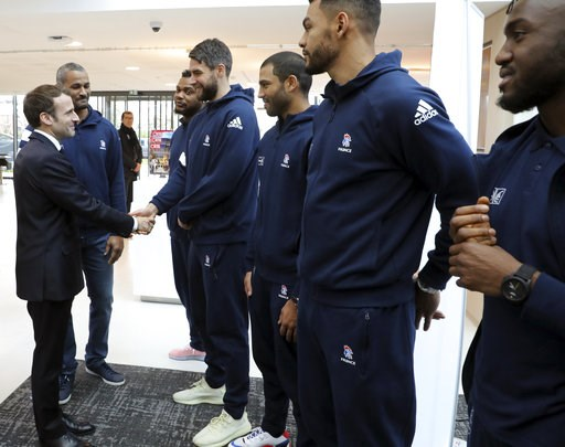 (Ludovic Marin, Pool via AP). French President Emmanuel Macron, left, shakes hands with national team players as he arrives to inaugurate a new handball stadium in Creteil, on the outskirts of Paris, Wednesday, Jan. 9, 2019. About 200 protesters, inclu...
