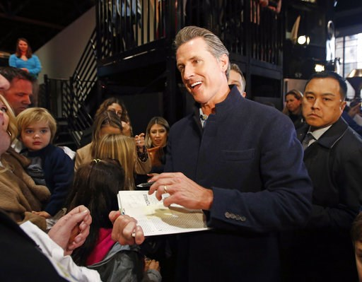 "(AP Photo/Rich Pedroncelli, File). FILE - In this Jan. 6, 2019 file photo, Gov.-elect Gavin Newsom autographs a copy of his book ""Citizenville"" for a wellwisher while attending a pre-inaugural Family Event held at the California Railroad Museum in Sacr..."