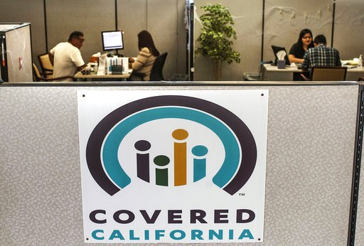 (Nick Agro/The Orange County Register/SCNG via AP, File). FILE - In this Nov. 1, 2016 file photo, agents help sign people up for insurance through the Covered California exchange at their storefront on Beach Boulevard in Huntington Beach, Calif. Califo...