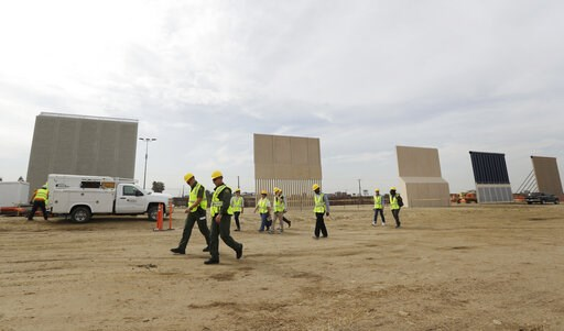 (AP Photo/Gregory Bull, File). File - In this Oct. 19, 2017 file photo, people pass border wall prototypes as they stand near the border with Tijuana, Mexico, in San Diego. Montana's Senate president is proposing the state give more than $8 million to ...