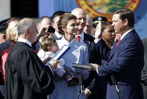 (AP Photo/Lynne Sladky). Ron DeSantis, right, is sworn in as Florida Governor by Chief Justice Charles Canady, left, as his wife Casey and son Mason look on, Tuesday, Jan. 8, 2019, in Tallahassee, Fla. Republicans will begin their third decade dominati...