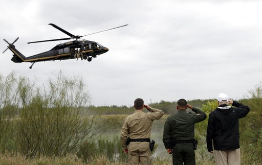 (AP Photo/ Evan Vucci). President Donald Trump salutes as a U.S. customs and Border Protection helicopter passes as he tours the U.S. border with Mexico at the Rio Grande on the southern border, Thursday, Jan. 10, 2019, in McAllen, Texas.