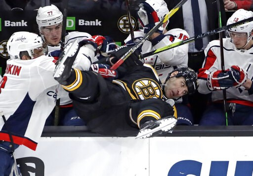 (AP Photo/Elise Amendola). Boston Bruins defenseman Zdeno Chara is checked into the Washington Capitals bench by Washington Capitals left wing Alex Ovechkin, left, during the first period of an NHL hockey game Thursday, Jan. 10, 2019, in Boston.