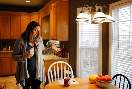 (AP Photo/David Goldman). Katie Barron gestures while looking at a pay increase notice for her children's day care, in her home in Madison, Ala., Wednesday, Jan. 9, 2019. Barron's husband is a National Weather Service meteorologist forced to work witho...