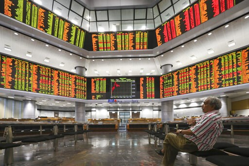 (AP Photo/Vincent Thian). Visitor watch a stock trading board at a private stock market gallery in Kuala Lumpur, Malaysia, Friday, Jan. 11, 2019. Asian markets were mostly higher on Friday as investors cheered a more reactive Federal Reserve and U.S.-C...