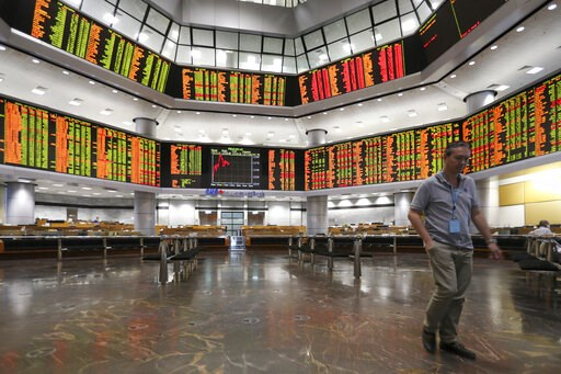 (AP Photo/Vincent Thian). Visitor walk under a stock trading board at a private stock market gallery in Kuala Lumpur, Malaysia, Friday, Jan. 11, 2019. Asian markets were mostly higher on Friday as investors cheered a more reactive Federal Reserve and U...