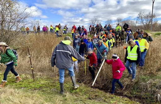 (AP Photo/Jeff Baenen, File). FILE - In this Oct. 23, 2018, file photo, volunteers cross a creek and barbed wire near Barron, Wis., on their way to a ground search for 13-year-old Jayme Closs who was discovered missing Oct. 15 after her parents were fo...