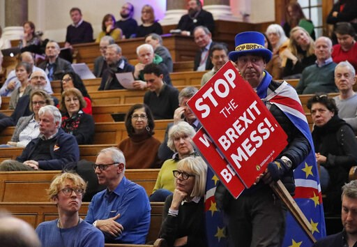 (AP Photo/Frank Augstein). A demonstrator enters the emergency, public gathering 'Think Anew, Act Anew: a Convention on Brexit and a People's Vote', in London, Friday, Jan. 11, 2019, ahead of the big parliamentary debate on the UK and the EU.