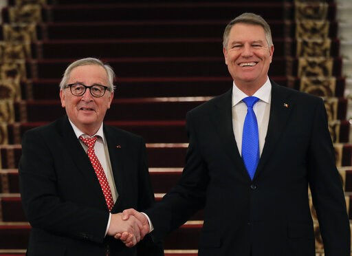 (AP Photo/Vadim Ghirda). European Union's Commission President Jean-Claude Juncker, left, shakes hands with Romanian President Klaus Iohannis at the Cotroceni palace in Bucharest, Romania, Friday, Jan. 11, 2019 during a visit marking the official start...