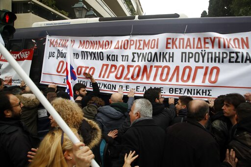 (AP Photo/Thanassis Stavrakis). Teachers and other protesters push police buses during clashes near the Prime Minister's office in Athens, Friday, Jan. 11, 2019. About 1,500 people took part in the protest. Teachers' unions oppose the government's sele...