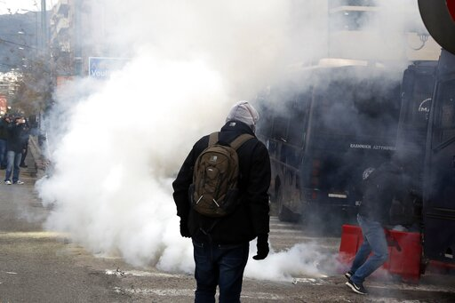 (AP Photo/Thanassis Stavrakis). Riot police throw a tear gas canister at teachers and other protesters, during clashes near the Prime Minister's office in Athens, Friday, Jan. 11, 2019. About 1,500 people took part in the protest. Teachers' unions oppo...