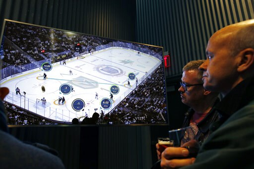 (AP Photo/John Locher). People watch real-time puck and player tracking technology on display during an NHL hockey game between the Vegas Golden Knights and the San Jose Sharks, in Las Vegas, Thursday, Jan. 10, 2019. The NHL for the first time has test...