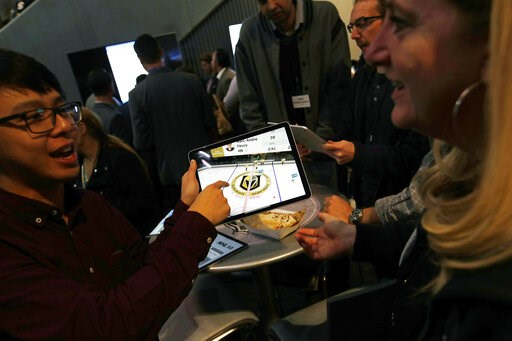 (AP Photo/John Locher). People watch real-time puck and player tracking technology on a tablet during an NHL hockey game between the Vegas Golden Knights and the San Jose Sharks in Las Vegas, Thursday, jan. 10, 2019. The NHL for the first time has test...