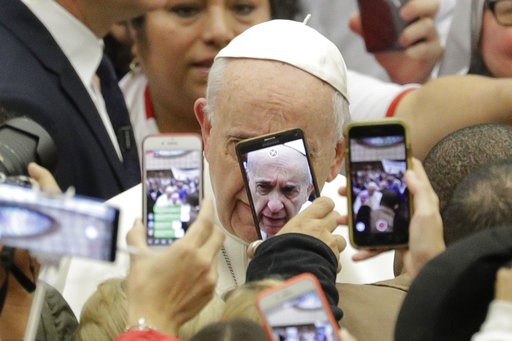 (AP Photo/Andrew Medichini). Pope Francis is framed by cellphones as he arrives for his weekly general audience, in the Pope Paul VI hall, at the Vatican, Wednesday, Jan. 9, 2019.