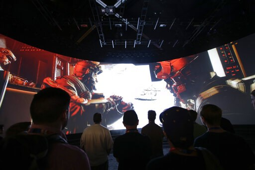 """(AP Photo/Jae C. Hong, File). FILE - In this June 12, 2014 file photo, people watch the """"Call of Duty: Advanced Warfare"""" video game trailer at the Activision booth at the Electronic Entertainment Expo, in Los Angeles.  Shares in video game publisher Ac..."""