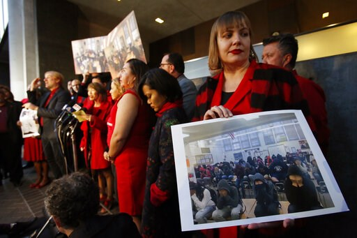 (AP Photo/Damian Dovarganes). United Teachers Los Angeles union representative Julie Van Winkle, right, holds a photograph with a class of 39 students covering their faces to avoid the need of parental releases, during a news conference outside the Los...
