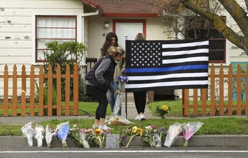 (AP Photo/Rich Pedroncelli). Sydney Carlier, foreground, accompanied by roommates, Jenna Brouwer, center and Camille Foder, behind flag, places flowers on a memorial for slain Davis Police Officer Natalie Corona, Friday, Jan. 11, 2019, in Davis, Calif....