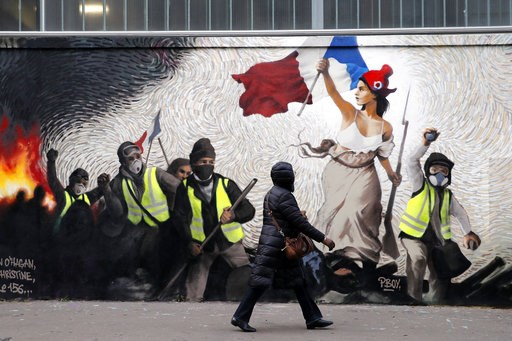 """(AP Photo/Christophe Ena). A woman passes by a mural by street artist PBOY depicting Yellow Vest (gilets jaunes) protestors inspired by a painting by Eugene Delacroix, """"La Liberte guidant le Peuple"""" (Liberty Leading the People), in Paris, Thursday, Jan..."""