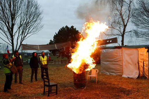 (AP Photo/Thibault Camus). Protestors wearing yellow vests stand next to a fire in a makeshift camp on a roundabout near Senlis, north of Paris, Thursday, Jan. 10, 2019. With its makeshift grocery, camp beds and community spirit, the large central isla...