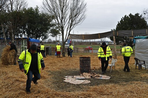 (AP Photo/Thibault Camus). Protestors wearing yellow vests stand in a makeshift camp on a roundabout near Senlis, north of Paris, Thursday, Jan. 10, 2019. With its makeshift grocery, camp beds and community spirit, the large central island about 60 kil...