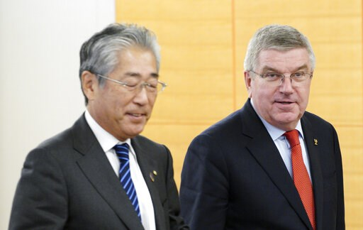 (AP Photo/Eugene Hoshiko, File). FILE - In this Nov. 30, 2018, file photo, International Olympic Committee (IOC) President Thomas Bach, right, escorts Japanese Olympic Committee (JOC) President Tsunekazu Takeda during an IOC Executive Board meeting in ...