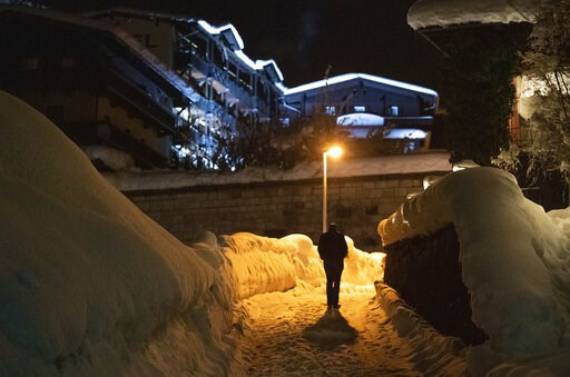 (Lino Mirgeler/dpa via AP). A person walks through the snow covered Bavarian city Berchtesgaden, early Saturday morning, Jan. 12, 2019.