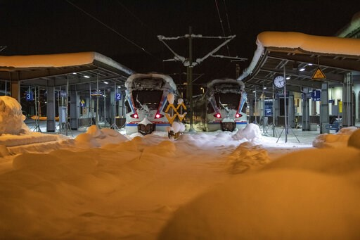 (Lino Mirgeler/dpa via AP). Two trains stand in a snowed-in railway station in the Bavarian city Berchtesgaden, Germany, Saturday, Jan. 12, 2019.
