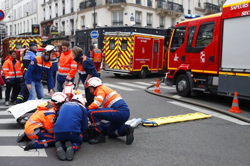 (AP Photo/Thibault Camus). Firefighters tends to a wounded person near the site of a gas leak explosion in Paris, France, Saturday, Jan. 12, 2019. A powerful explosion and fire apparently caused by a gas leak at a Paris bakery Saturday injured several ...