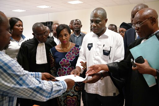 (AP Photo/Jerome Delay). Accompanied by his wife and his lawyers, Congo opposition candidate Martin Fayulu receives the receipt after petitioning the constitutional court following his loss in the presidential elections in Kinshasa, Congo, Saturday Jan...