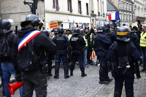 (AP Photo/Rafael Yaghobzadeh). French police, one wearing a ribbon in the colors of the French flag, block a demonstration of yellow vest protestors in Bourges, central France, Saturday, Jan. 12, 2019. Paris brought in armored vehicles and the central ...