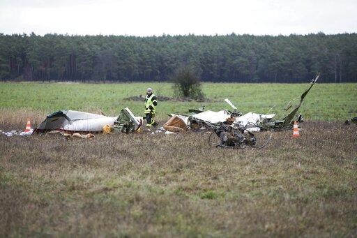 (Joerg Carstensen/dpa via AP). A man walks through the scene of a small plane crash on a field near the village Praedikow, about 50 kilometers, 31 miles, east of Berlin, Germany, Saturday, Jan. 12, 2019.