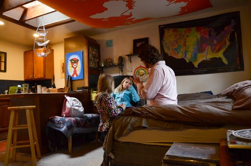 (AP Photo/Tatiana Flowers, File). FILE - In this Nov. 28, 2017, file photo, TC Bell sits with his two daughters Dagny, and Emma, before they get dressed for school, at their home in Denver. Bell's daughters were then recipients of the Children's Health...