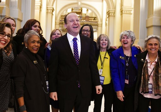 (AAron Ontiveroz/The Denver Post via AP, File). FILE - In this Tuesday, Jan. 8, 2019, file photo, Colorado Governor elect Jared Polis, center, jokes with members of the state house and senate before his inauguration at the Colorado State Capitol in Den...