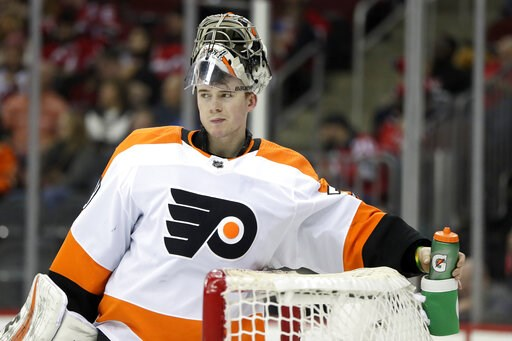 (AP Photo/Julio Cortez). Philadelphia Flyers goaltender Carter Hart grabs his water bottle between plays against the New Jersey Devils during the second period of an NHL hockey game, Saturday, Jan. 12, 2019, in Newark, N.J.