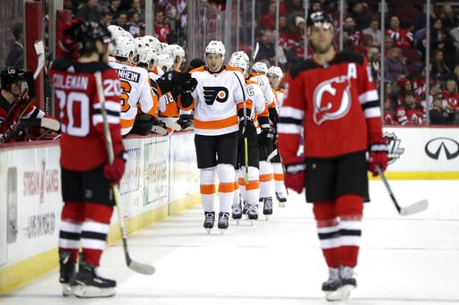 (AP Photo/Julio Cortez). Philadelphia Flyers left wing James van Riemsdyk, center, skates by the bench after scoring a goal on the New Jersey Devils during the second period of an NHL hockey game, Saturday, Jan. 12, 2019, in Newark, N.J.