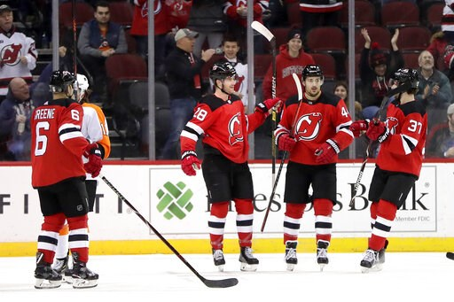 (AP Photo/Julio Cortez). New Jersey Devils defenseman Damon Severson, second from left, celebrates his first period with teammates during an NHL hockey game against the Philadelphia Flyers, Saturday, Jan. 12, 2019, in Newark, N.J.