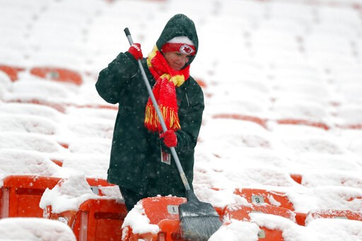 (AP Photo/Charlie Neibergall). A groundskeeper brushes snow off of seats at Arrowhead Stadium before an NFL divisional football playoff game against the Indianapolis Colts in Kansas City, Mo., Saturday, Jan. 12, 2019.