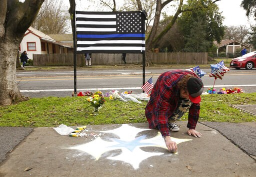 (AP Photo/Rich Pedroncelli). Matthew Ottele draws a star on the sidewalk Friday, Jan. 11, 2019, near the scene were Davis Police Officer Natalie Corona was shot and killed in Davis, Calif. Corona, 22, who had been on the job only a few weeks was slain,...