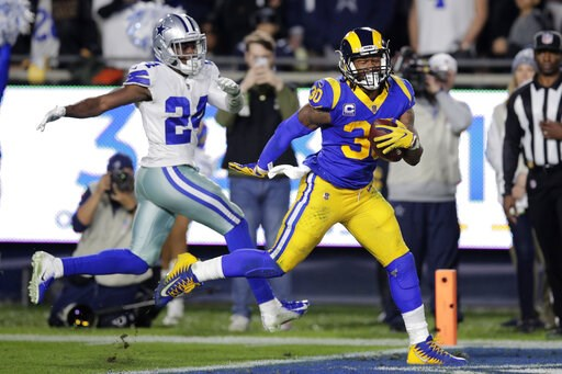 (AP Photo/Jae C. Hong). Los Angeles Rams running back Todd Gurley scores past Dallas Cowboys cornerback Chidobe Awuzie during the first half in an NFL divisional football playoff game Saturday, Jan. 12, 2019, in Los Angeles.
