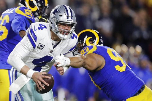 (AP Photo/Jae C. Hong). Dallas Cowboys quarterback Dak Prescott breaks away from Los Angeles Rams nose tackle Ndamukong Suh during the first half in an NFL divisional football playoff game Saturday, Jan. 12, 2019, in Los Angeles.