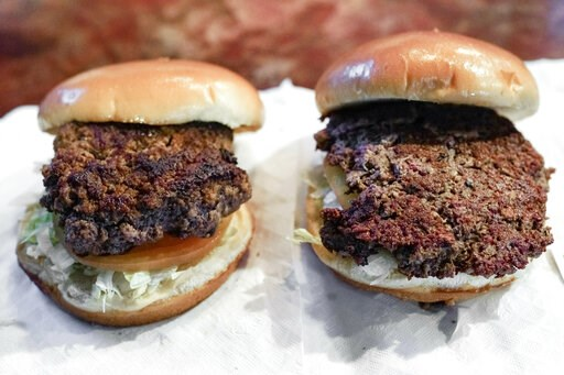 """(AP Photo/Nati Harnik). A conventional beef burger, left, is seen Friday, Jan. 11, 2019, next to """"The Impossible Burger"""", right, a plant-based burger containing wheat protein, coconut oil and potato protein among it's ingredients. The ingredients of th..."""