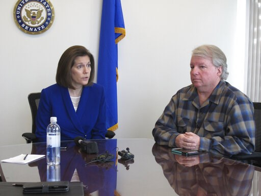 (AP Photo/Scott Sonner). David Pritchett, a furloughed worker for the U.S. Bureau of Land Management, looks on as Sen. Catherine Cortez Masto, D-Nev., talks to reporters Friday, Jan. 11, 2019, in her office in Reno about the impacts of the partial gove...