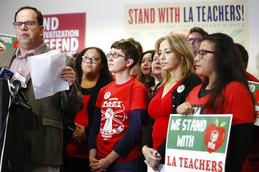 (AP Photo/Damian Dovarganes). United Teachers Los Angeles president and teacher, Alex Caputo-Pearl, far left, at podium, announces the nation's second-largest school district will go on strike Monday at a news conference in Los Angeles Sunday, Jan. 13,...