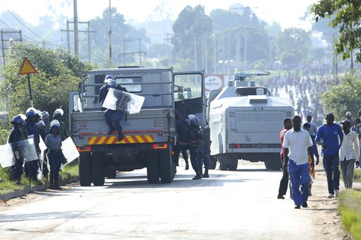 (AP Photo/Tsvangirayi Mukwazhi). Riot police are seen on a street during a demonstration over the hike in fuel prices in Harare, Zimbabwe, Monday, an. 14, 2019. Zimbabwean President Emmerson Mnangagwa has more than doubled the price of gasoline, hoping...