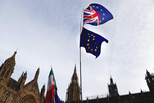 (AP Photo/Frank Augstein). A Pro-European demonstrator raises flags to protest outside parliament in London, Friday, Jan. 11, 2019. Britain's Prime Minister Theresa May is struggling to win support for her Brexit deal in Parliament. Lawmakers are due t...