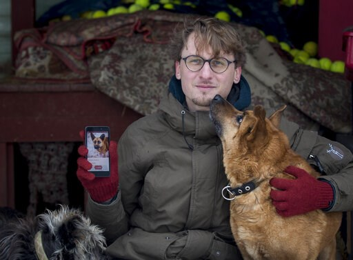 (AP Photo/Mindaugas Kulbis). In this photo taken on Saturday, Feb. 2, 2019, Vaidas Gecevicius, who developed an app helping to match stray dogs with potential owners, poses for a picture with a dog and shows this dog's profile on the app in Vilnius, Li...