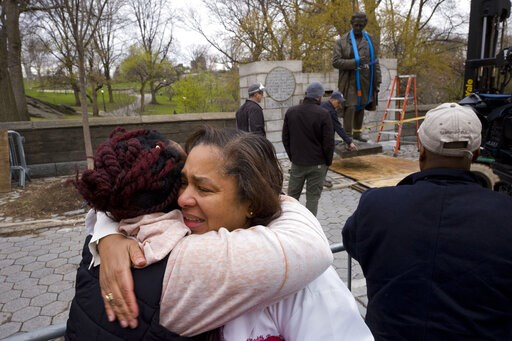 (AP Photo/Mark Lennihan, File). FILE - In this Tuesday, April 17, 2018, file photo, Dr. Bernadith Russell hugs a friend as the statue of Dr. J. Marion Sims, is removed from New York's Central Park. Sims was known as the father of modern gynecology, but...