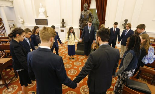 (AP Photo/Steve Helber). In this Feb. 5, 2019, photo, a group of students from the Teenpact Leadership school pray in front of the statue of Confederate General Robert E. Lee in the old House chambers at the Capitol in Richmond, Va. Virginia has come a...